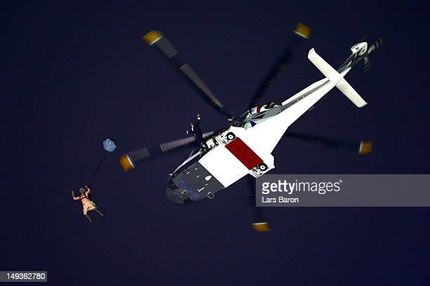 A performer in the role of Queen Elizabeth II parachutes out of a helicopter hovering above the stadium during the Opening Ceremony of the London...