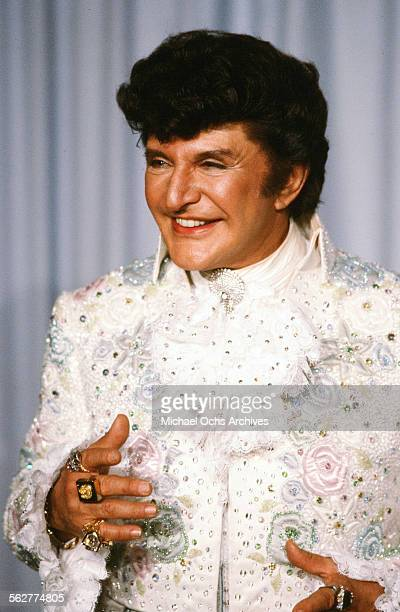 Performer Liberace poses backstage after performing 'Endless Love' during the 54th Academy Awards at Dorothy Chandler Pavilion in Los...
