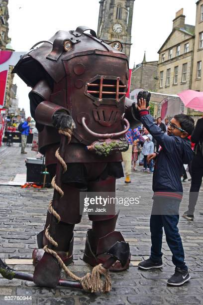 A performer on the Royal Mile gives a young boy a 'high five' during the Edinburgh Festival Fringe on August 16 2017 in Edinburgh Scotland The Fringe...