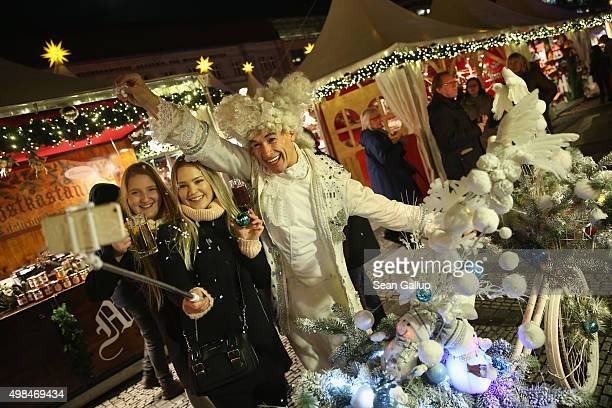 A performer poses for a selfie with two visitors from Finland at the annual Christmas market at Gendarmenmarkt on its opening day on November 23 2015...