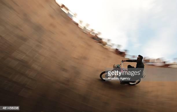 A performer rides a motorbike on the Wall of Death at Nawaz Sharif Park in Rawalpindi Pakistan on July 20 2015