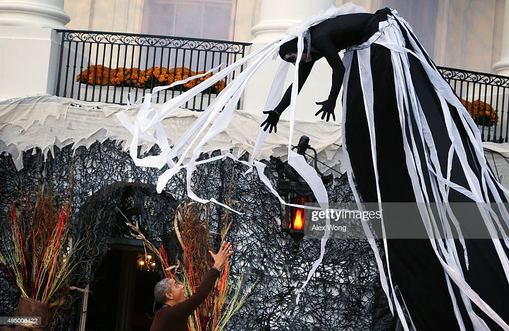 A performer suspended above U.S. President Barack Obama (L) during a Halloween event at the South Lawn of the White House October 30, 2015 in Washington, DC. The first couple hosted local children and children of military families for trick-or-treating at the White House.