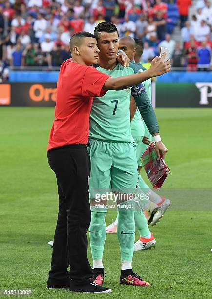 A performer takes a selfie with Cristiano Ronaldo of Portugal before the UEFA EURO 2016 semi final match between Portugal and Wales at Stade des...