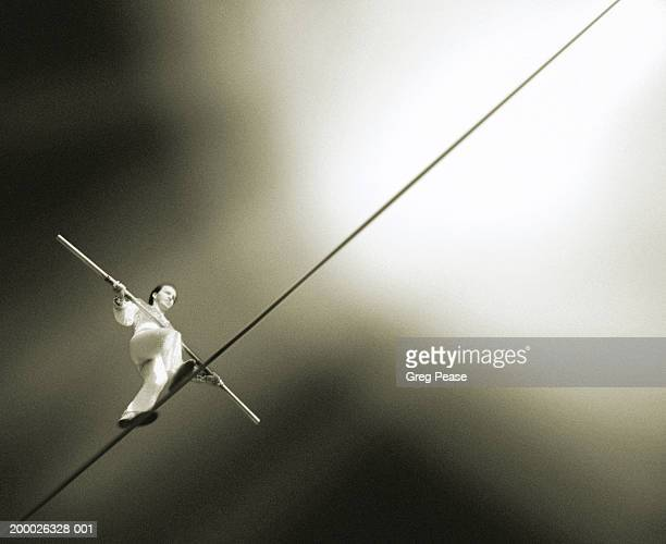Performer walking tightrope, low angle view (grainy, infrared B&W)