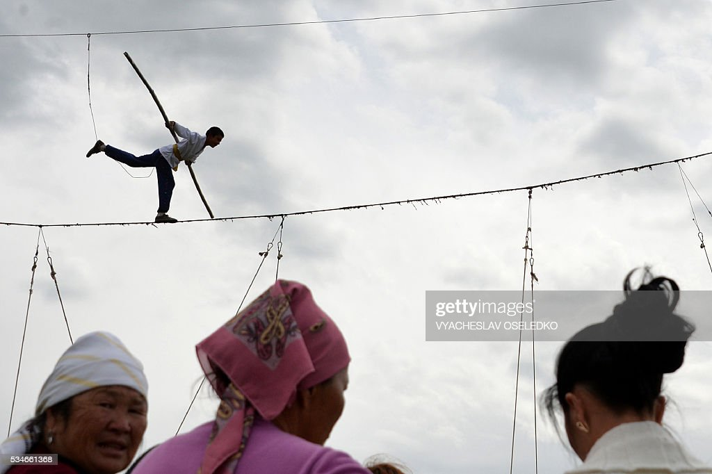 A performer walks on a tightrope during the celebrations of the 90th anniversary formation of the Chui region in the village of Kuntu some 20 kms from Bishkek on May 27, 2016. / AFP / VYACHESLAV