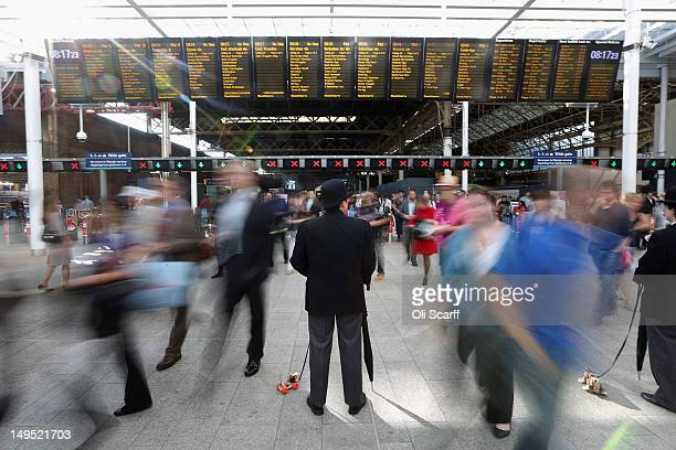 A performer wearing a bowler hat greets rail passengers making their way through London Bridge Station on July 30 2012 in London England London's...