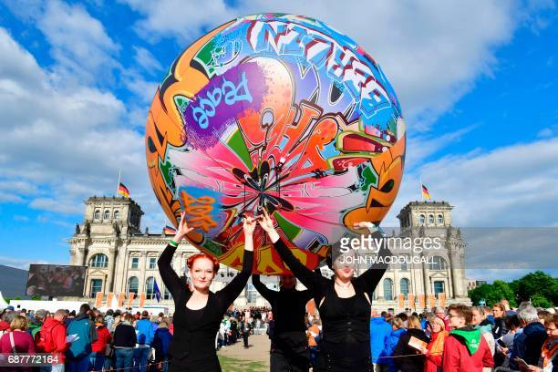 Performers carry a giant graffiti ball in front of the Reichstag building that houses Germany's Bundestag lower house of parliament in Berlin on May...