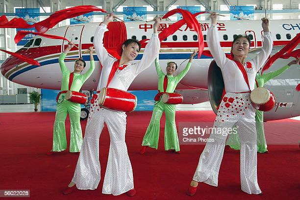 Performers dance during a ceremony of China Eastern Airlines to take delivery of its 100th airbus an A320 at Shanghai Hongqiao International Airport...