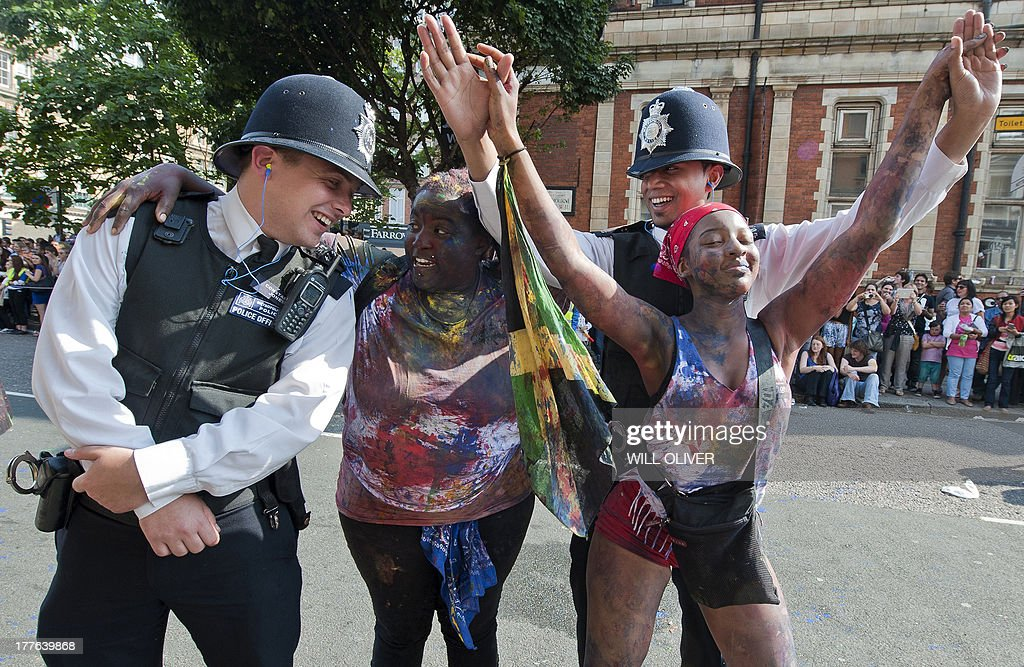 Performers dance with police officers on the first day of the Notting Hill Carnival in west London on August 25, 2013. Running over two days, the Caribbean carnival puts on a Kid's day on the Sunday when costume prizes are awarded and a 'main parade' day on the Monday.