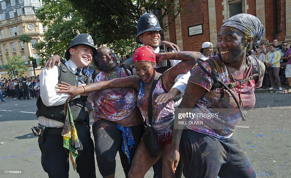 Performers dance with police officers on the first day of the Notting Hill Carnival in west London on August 25, 2013. Running over two days, the Caribbean carnival puts on a Kid's day on the Sunday when costume prizes are awarded and a 'main parade' day on the Monday. AFP PHOTO / WILL OLIVER