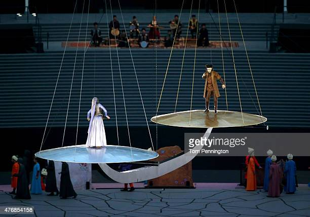 Performers depicting the charcters Leyli and Majnun from the poetry of Nizami dance on giant measuring scales during the Opening Ceremony for the...