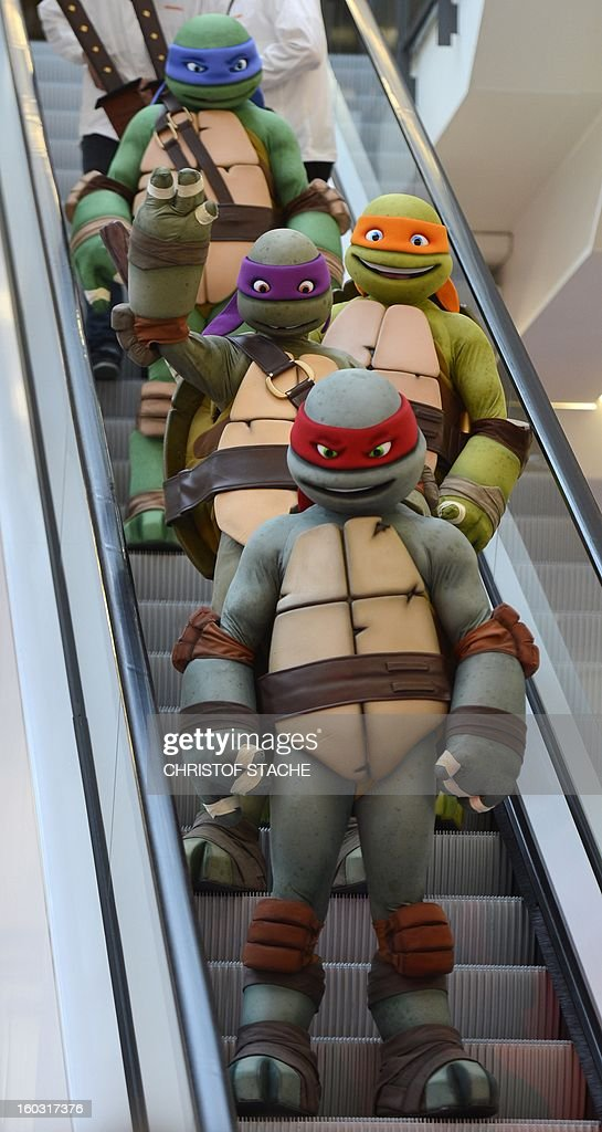 Performers dressed as Ninja Turtles figures stand at an escalator during the press preview of the international toy fair in Nuremberg, southern Germany, on January 29, 2013. Around 2.700 exhibitors show more than 1 million products at the international toy fair which opens its doors from January 29 to February 4, 2013.
