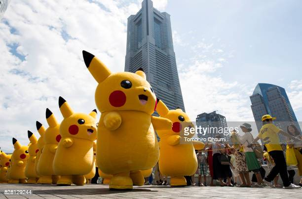 Performers dressed as Pikachu a character from Pokemon series game titles march during the Pikachu Outbreak event hosted by The Pokemon Co on August...