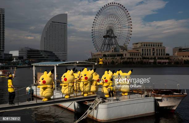 Performers dressed as Pikachu a character from Pokemon series game titles walk on a pier after riding on a boat during the Pikachu Outbreak event...