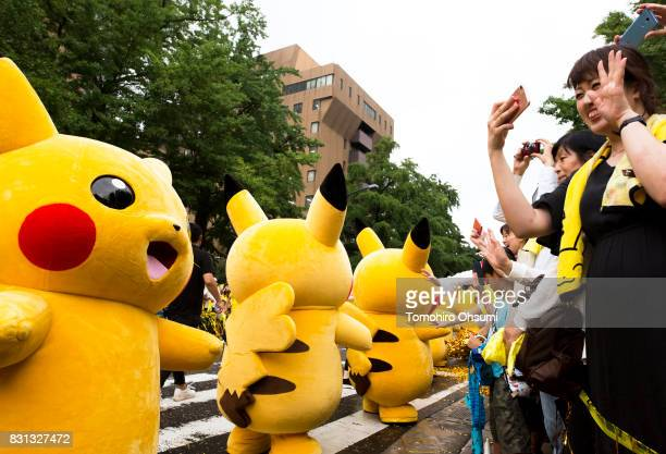 Performers dressed as Pikachu a character from Pokemon series game titles march during a parade as part of the Pikachu Outbreak event hosted by The...