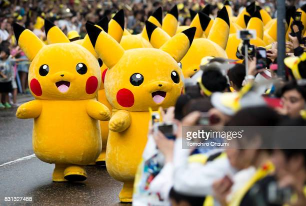 Performers dressed as Pikachu a character from Pokemon series game titles march during a parade held as part of the Pikachu Outbreak event hosted by...