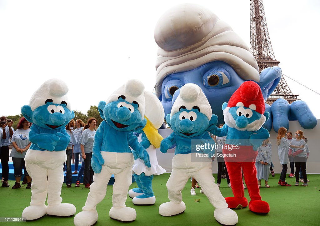 Performers dressed up as Smurf characters pose by a giant Smurf character as part of Global Smurfs Day celebrations on June 22, 2013 on the Seine river bank in Paris, France. The Eiffel tower is seen behind.