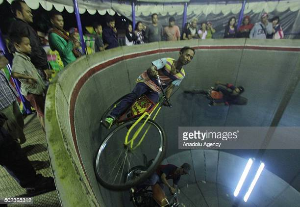 Performers drive a motorcycle and bicycles on the Wall of Death at the night market in Surakarta Central Java Indonesia on December 23 2015