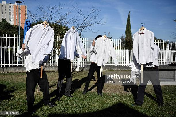 TOPSHOT Performers from a small theater company hold shirts as they rehearse their act near the Bobigny courthouse northeast of Paris on September 27...