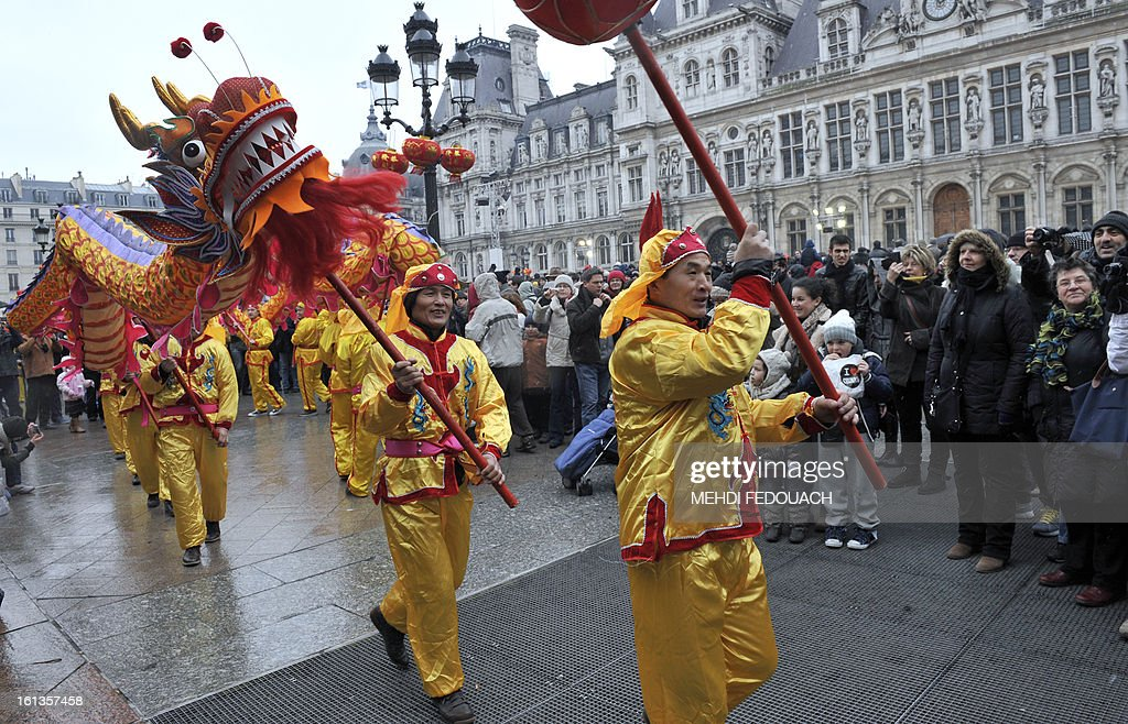 Performers hold a dragon as they dance during a parade in front of Paris City Hall on February 10, 2013, to celebrate Chinese New Year. Chinese communities world wide traditionally welcomed in the 'Year of the Snake'. AFP PHOTO / MEHDI FEDOUACH