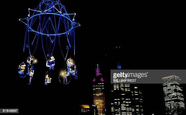 Performers in the French theatre company 'Transe Express' are suspended high above the Melbourne skyline in a performance which is described as...
