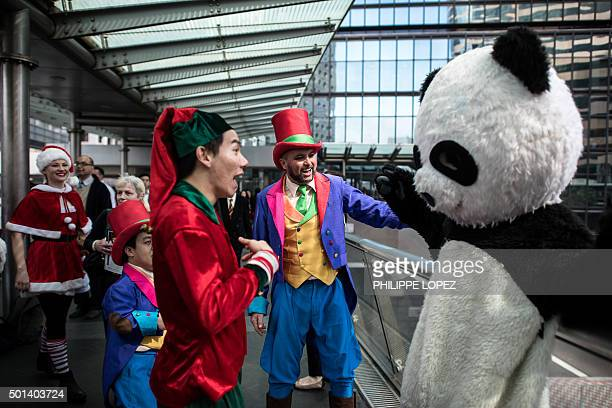 Performers meet a man dressed in a panda costume as they parade in Hong Kong on December 15 2015 to promote a funfair and festival taking place...