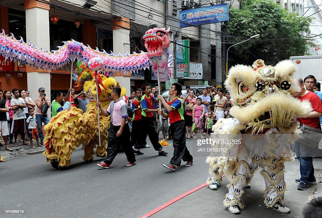 Performers perform a lion dance (R) and a dragon dance on the eve of the Chinese Lunar New Year of the Snake, in China town in Manila on February 9, 2013. The Dragon Dance is usually performed during the Chinese New Year to bring in good luck and prosperity as billions of Chinese world wide celebrate Lunar New Year of the Snake on February 10. AFP PHOTO / Jay DIRECTO