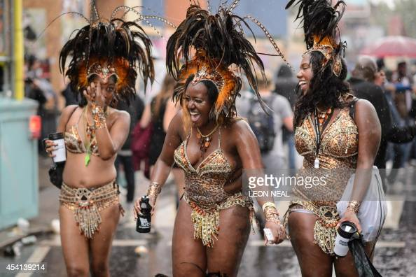 Performers share a joke as they parade on the second day of the Notting Hill Carnival in west London on August 25 2014 Heavy rain continued...
