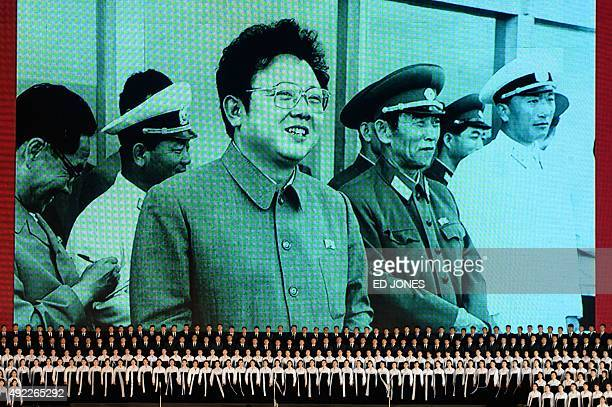 Performers sing before a giant television screen showing late North Korean leader Kim JongIl during an open air dance and music performance on the...