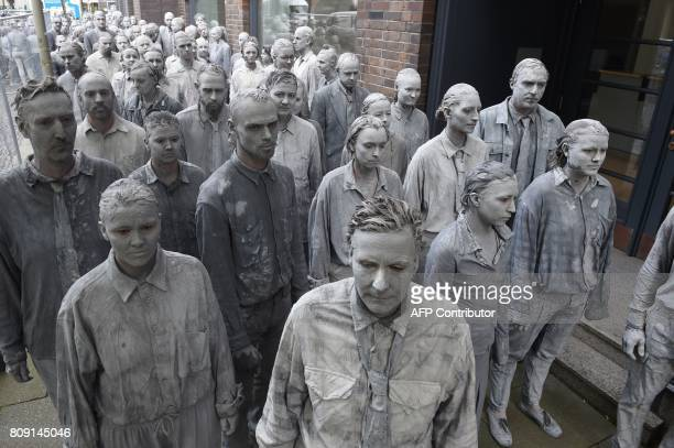 Performers smeared with clay demonstrate during the art action '1000 Gestalten' on July 5 2017 on a street in Hamburg northern Germany where leaders...