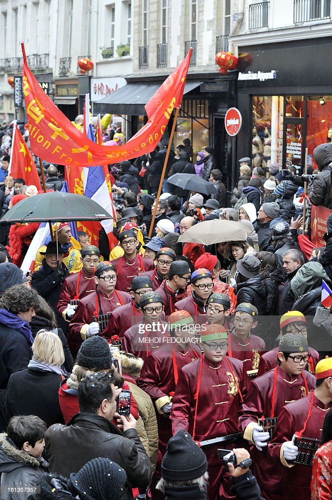 Performers surrounded by the crowd celebrate Chinese New Year on February 10, 2013 during a parade in Paris. Chinese communities world wide traditionally welcomed in the 'Year of the Snake'. AFP PHOTO / MEHDI FEDOUACH