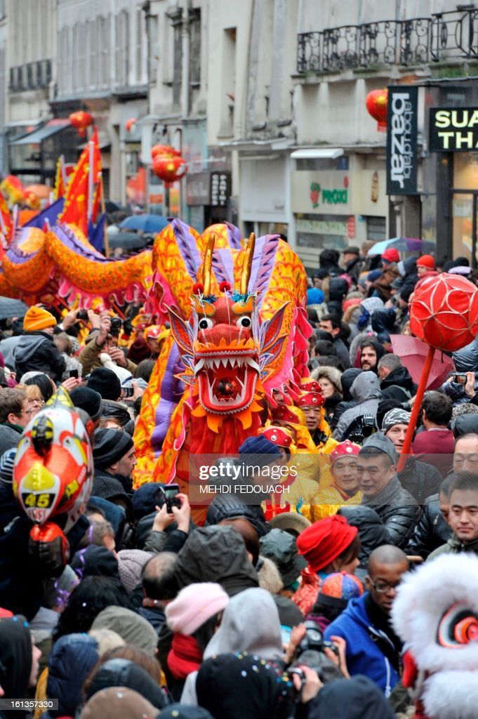 Performers surrounded by the crowd hold a dragon as they dance during a parade in Paris on February 10, 2013, to celebrate Chinese New Year. Chinese communities world wide traditionally welcomed in the 'Year of the Snake'.