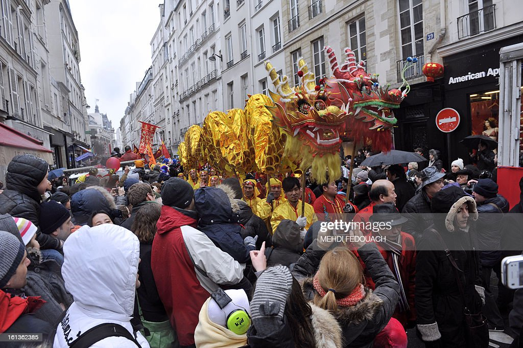 Performers surrounded by the crowd hold a dragon as they dance during a parade in Paris on February 10, 2013, to celebrate Chinese New Year. Chinese communities world wide traditionally welcomed in the 'Year of the Snake'. AFP PHOTO / MEHDI FEDOUACH