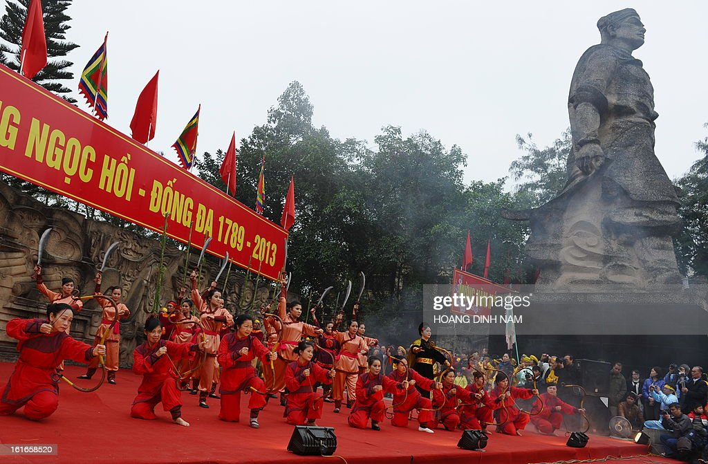 Performers take part in a ceremony next to a statue of King Quang Trung (R) to mark the 224th anniversary of Vietnam's Dong Da victory over Chinese invading troops in the spring of 1789 at the site of the historical battlefield in Hanoi on February 14, 2013. AFP PHOTO/HOANG DINH Nam