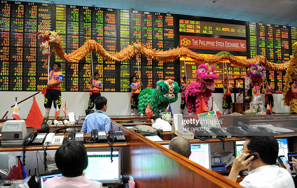 Performers take part in a dragon and lion dance at the Philippine Stock Exchange to mark the start of the first day of trading in the Chinese Lunar New Year of the Snake in Manila on February 11, 2013. The Philippine stock market has been repeatedly hitting new record highs in recent months, lifted by the country's bright economic prospects, lots of liquidity and interest from abroad. The Dragon Dance is usually performed during the Chinese New Year to bring in good luck and prosperity as billions of Chinese world wide celebrate the Lunar New Year. AFP PHOTO / Jay DIRECTO
