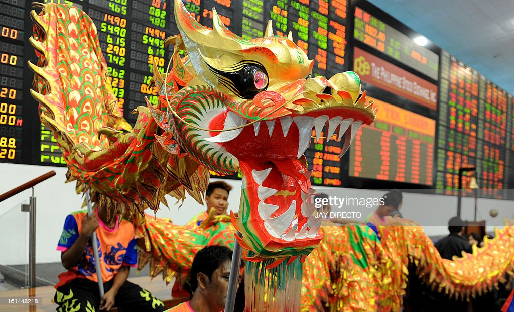 Performers take part in a dragon dance at the Philippine Stock Exchange to mark the start of the first day of trading in the Chinese Lunar New Year of the Snake in Manila on February 11, 2013. The Philippine stock market has been repeatedly hitting new record highs in recent months, lifted by the country's bright economic prospects, lots of liquidity and interest from abroad. The Dragon Dance is usually performed during the Chinese New Year to bring in good luck and prosperity as billions of Chinese world wide celebrate the Lunar New Year. AFP PHOTO / Jay DIRECTO