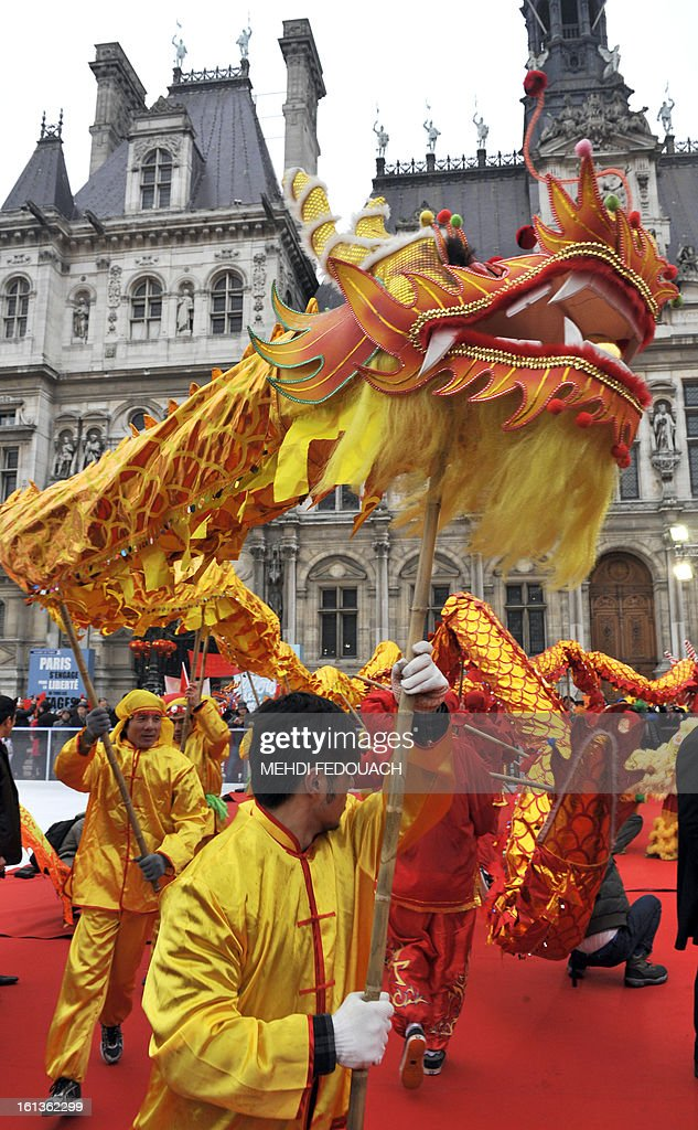 Performers take part in a dragon dance in front of Paris City Hall to celebrate Chinese New Year on February 10, 2013, before parading in Paris' streets. Chinese communities world wide traditionally welcomed in the 'Year of the Snake'. AFP PHOTO / MEHDI FEDOUACH