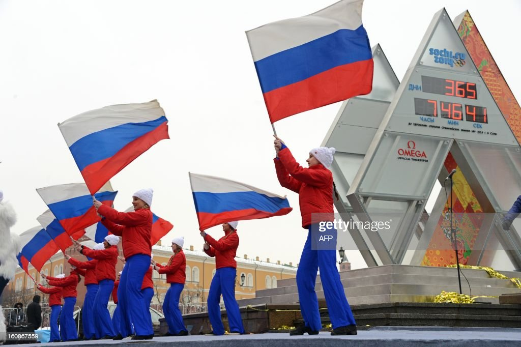Performers wave Russian flags near the Sochi 2014 countdown clock just outside the Kremlin in Moscow, on February 7, 2013, shortly after the clock unveiling. The clock screens display number of days (top) and time (hours, minutes, seconds) left to the opening of the Winter Olympics in Sochi.