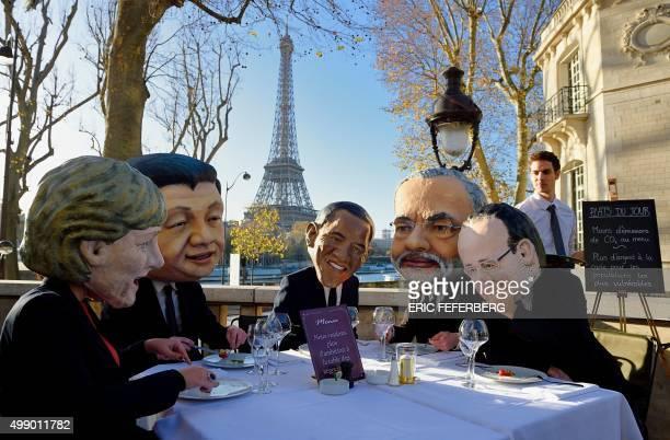 Performers wearing effigies of world leaders German Chancellor Angela Merkel China's President Xi Jinping US President Barack Obama Indian Prime...
