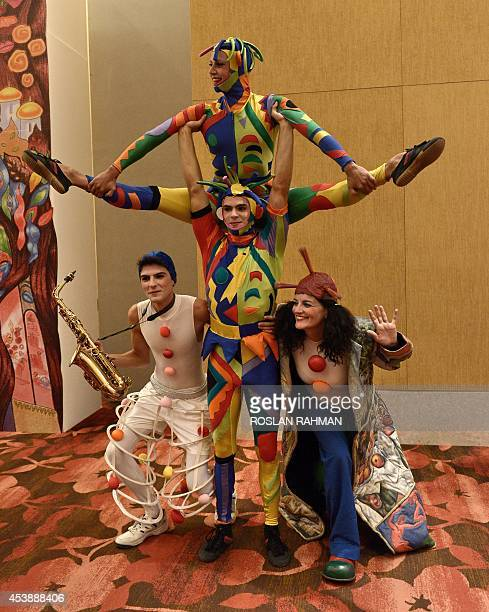 Performers welcome guests at the entrance to an exhibition for the Fantasia by Escriba during a media preview in Singapore on August 21 2014 The...