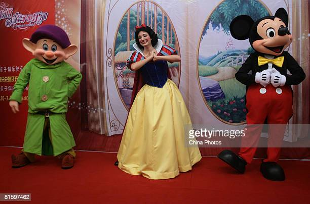 Performers who act as the Dwarf Snow White and Mickey Mouse pose during a press conference to promote Disney drama 'Three Classic Fairy Tales' on...