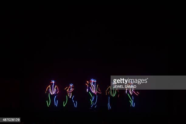 Performers with lights on their costumes perform on stage during the fourth and final day of the 15th International Indian Film Academy Awards at the...