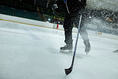 Low angle view of an unrecognisable person doing a hockey-stop and making the ice spray.