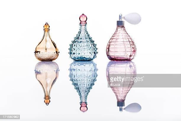 studio di bottiglie di profumo su bianco con riflessione