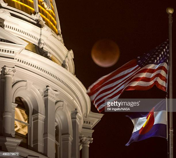 A perigee full moon or supermoon is seen during a total lunar eclipse behind the Colorado State Capitol building on September 27 in Denver Colorado...