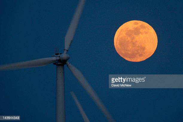 A perigee moon or supermoon rises behind wind turbines on May 5 2012 near Palm Springs California The moon appears especially big and bright during...