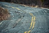 Permafrost damage to a road in the Canadian arctic.  Buckled pavement and copy space.
