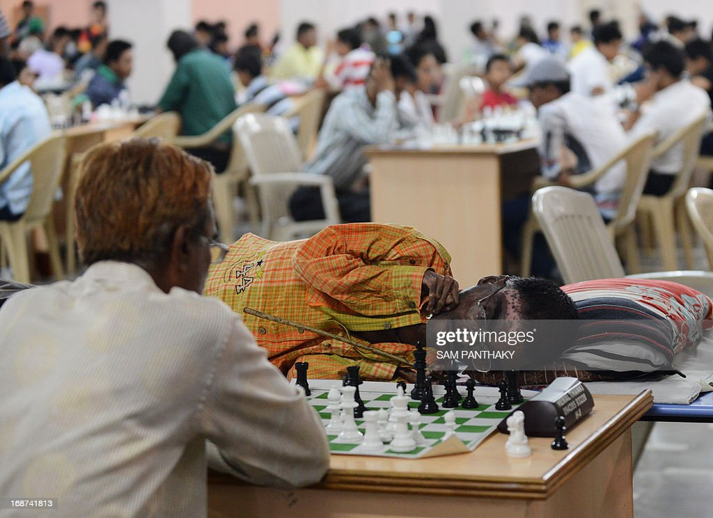 Permanently bed-ridden, Shailesh Nerlikar (C), 32, from Maharashtra plays chess against Mukesh Parmar (L) of Surendranagar, Gujarat, on the first day of the Brain Power U-2000 International Rating Tournament, at the SGVP International School on the outskirts of Ahmedabad on May 14, 2013. Shailesh was disabled when he was given the wrong dose of medicines by a doctor when he was six years old. Shailesh was lifted by his mother Sarala Nerlikar when he entered the Chess tournament where over 340 players from across India are participating. The current Chess Rating of Shailesh Nerlikar is 1698. AFP PHOTO / Sam PANTHAKY