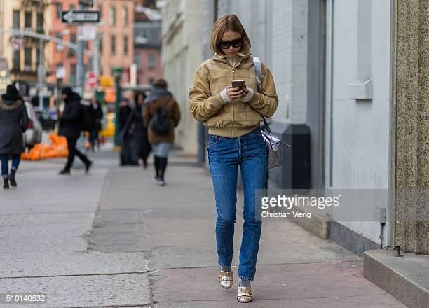 Pernille Teisbaek wearing a beige jacket blue denim jeans golden heels and a silver bag seen outside Jason Wu during New York Fashion Week Women's...
