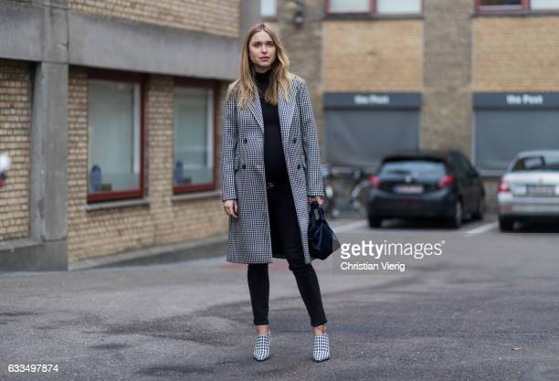 Pernille Teisbaek wearing a checked coat Gucci belt checked heels black denim jeans outside Baum Pferdgarten at the Copenhagen Fashion Week...